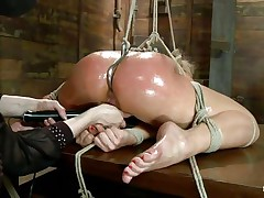 Oiled up blonde is tied up and has a hook in her anus. She is getting her pussy fingered hard by this women and she is bursting with pleasure as she fingers her deeper and deeper while using that vibrator on her clitoris. Those oiled sexy thighs are spread and tied very hard and you can clearly see that cum asking shaved pussy between them. In the next scene she's hanging with her sexy legs spread even wider, what do you think she will endure?